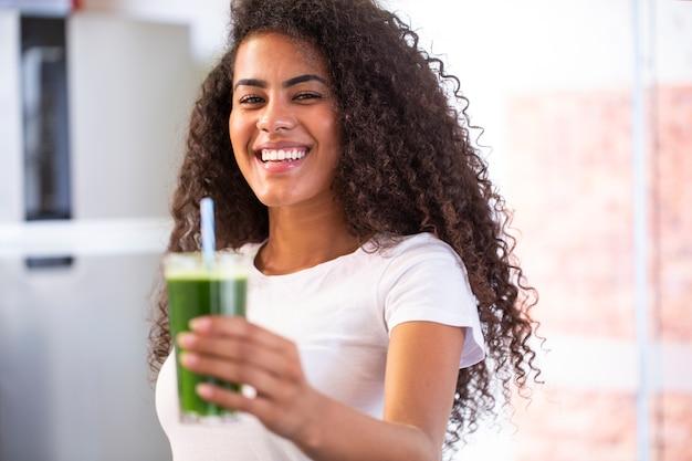 Junge afrikanische frau genießen gesunden vegetarischen smoothie für gewichtsverlust und entgiftung