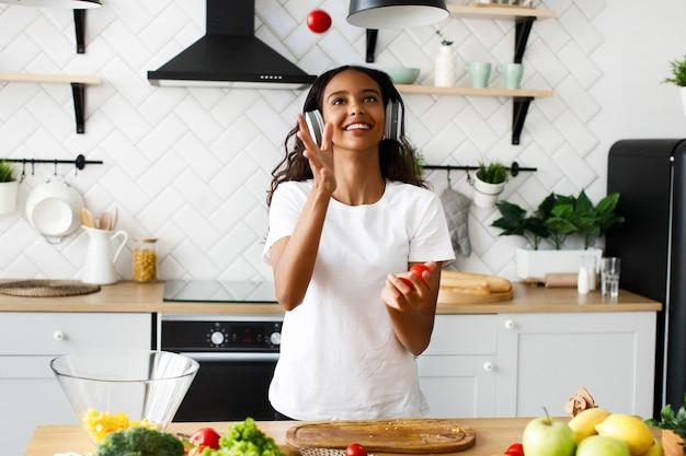 Junge afrikanische frau hört musik in den kopfhörern und jongliert kirschtomaten in der küche