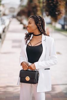 Junge afrikanische frau kleidete im weißen anzug außerhalb der straße an