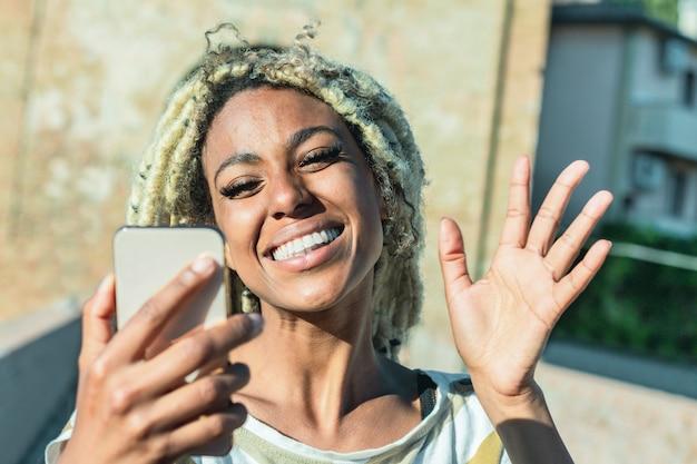 Junge afrikanische frau mit blonden dreadlocks, die videoanruf mit intelligentem handy tun