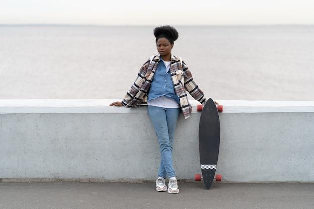 Junge afrikanische frau mit trendigem longboard über dem fluss, die sich nach dem skateboarden auf der promenade erholt?