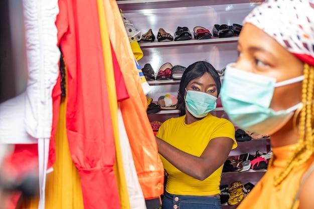 Junge afrikanische frauen kaufen kleidung in einem lokalen geschäft?
