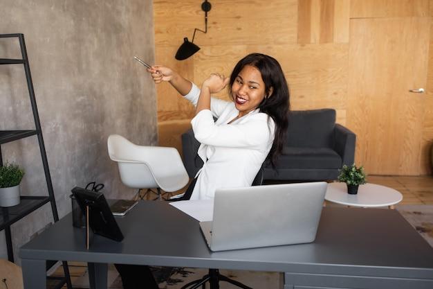 Junge afrikanische geschäftsfrau tragen kopfhörer studie online ansehen webinar podcast auf laptop hören lernen bildung kurs konferenzanruf machen notizen am schreibtisch sitzen e-learning-konzept sitzen
