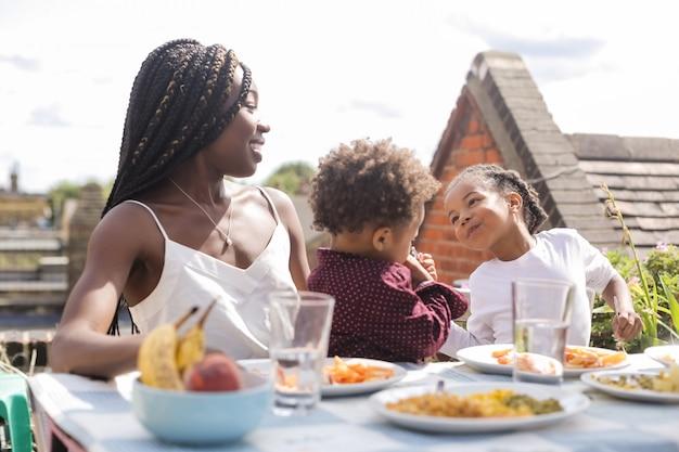 Junge afrikanische jungen, die mahlzeit mit mutter essen