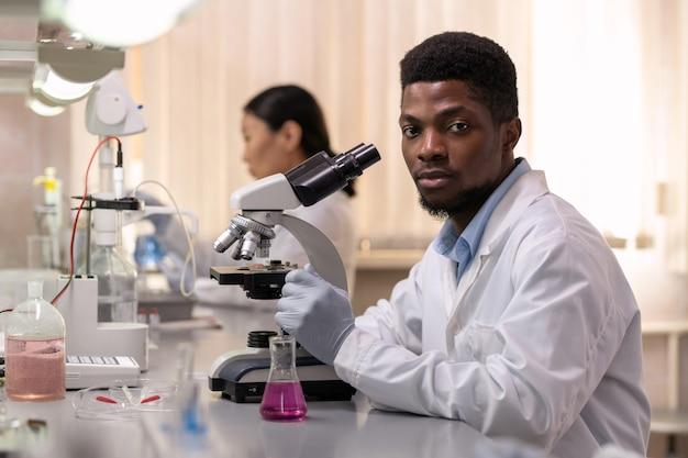 Junge afrikanische männliche chemiker mit mikroskop sitzen am schreibtisch im labor