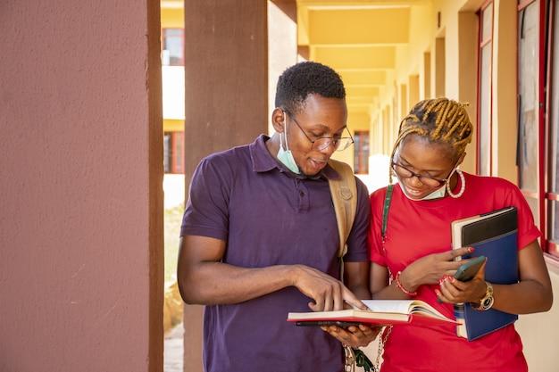 Junge afrikanische studenten, die gesichtsmasken tragen und bücher und telefone auf einem campus halten