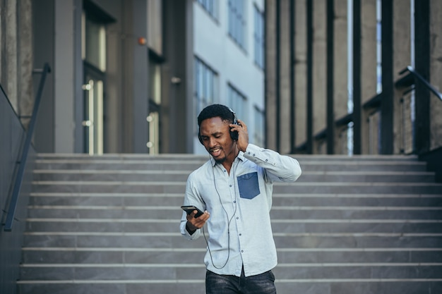Junge afrikanische studentin, die mit großen kopfhörern musik vom smartphone hört und von der bequemlichkeit der verwendung der app lächelt