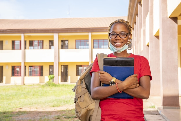 Junge afrikanische studentin mit gesichtsmaske, die ihre lehrbücher auf einem campus hält