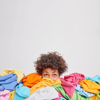 Junge afro-amerikanerin, die von verschiedenen bunten kleidern umgeben ist, sortiert die garderobe aus, die oben isoliert über der weißen wand leer ist, für ihre werbeinhalte nichts zu tragen konzept