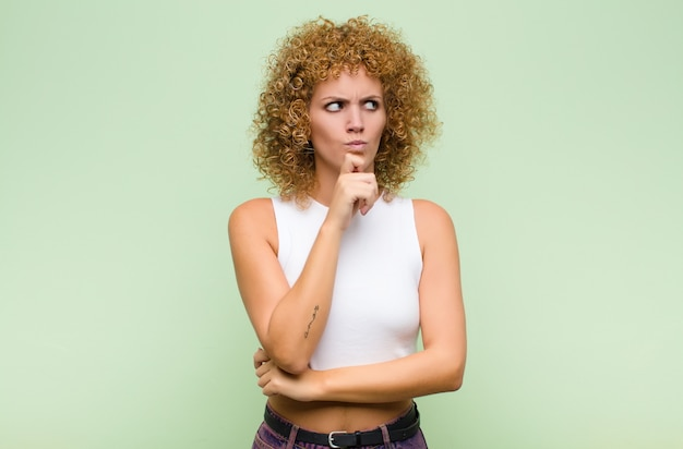 Junge afro-frau denkt, fühlt sich zweifelhaft und verwirrt, mit verschiedenen optionen, und fragt sich, welche entscheidung sie gegen die grüne wand treffen soll