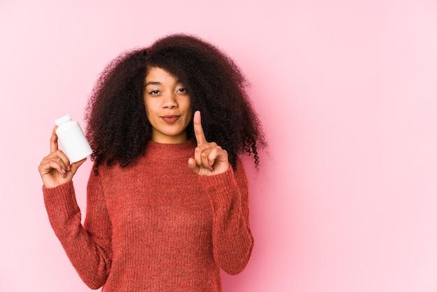 Junge afro-frau, die ein isoliertes vitamin hält junge afro-frau, die ein vitamin hält, das nummer eins mit finger zeigt.