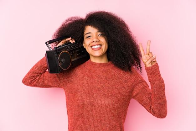 Junge afro-frau, die eine kassette hält, die nummer zwei mit den fingern zeigt.