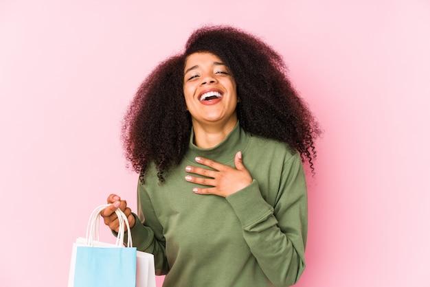 Junge afro-frau, die einkaufstasche hält, lacht laut und hält hand auf brust