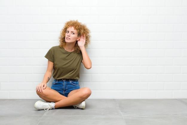 Junge afro-frau, die ernst und neugierig aussieht, zuhört, versucht, ein geheimes gespräch oder klatsch zu hören, lauschend auf einem boden sitzend