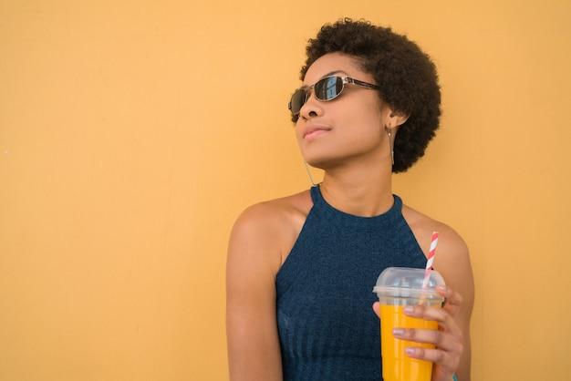 Junge afro-frau, die frischen fruchtsaft trinkt.