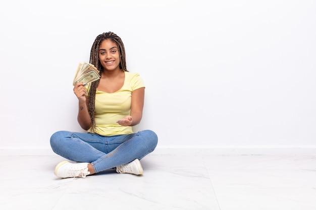 Junge afro-frau, die glücklich mit freundlichem, selbstbewusstem, positivem blick lächelt und ein objekt oder konzept anbietet und zeigt. geldkonzept