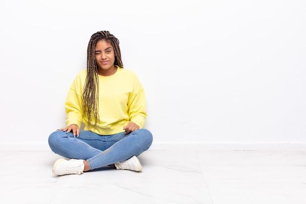 Junge afro-frau, die glücklich und freundlich schaut, lächelt und ein auge zwinkert