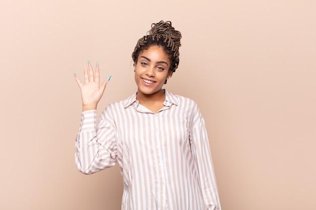 Junge afro-frau, die glücklich und fröhlich lächelt und hand winkt