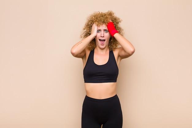 Junge afro-frau, die hände zum kopf hebt, mit offenem mund, sich extrem glücklich, überrascht, aufgeregt und glückliches sportkonzept fühlt