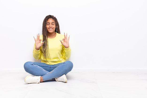 Junge afro-frau, die konzentriert und meditierend aussieht, sich zufrieden und entspannt fühlt, denkt oder eine wahl trifft