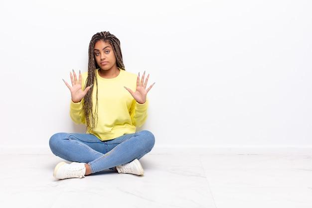 Junge afro-frau, die nervös, ängstlich und besorgt aussieht
