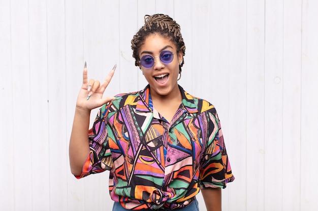 Junge afro-frau, die sich glücklich, lustig, selbstbewusst, positiv und rebellisch fühlt und mit der hand rock- oder heavy-metal-zeichen macht