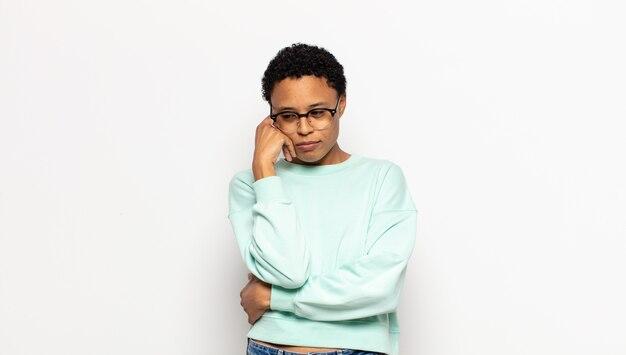 Junge afro-frau, die sich nach einer ermüdenden, langweiligen und mühsamen aufgabe gelangweilt, frustriert und schläfrig fühlt und das gesicht mit der hand hält