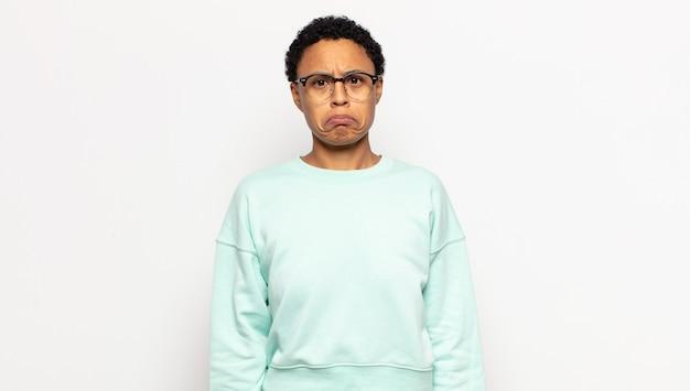 Junge afro-frau, die sich traurig und weinerlich mit einem unglücklichen blick fühlt und mit einer negativen und frustrierten haltung weint