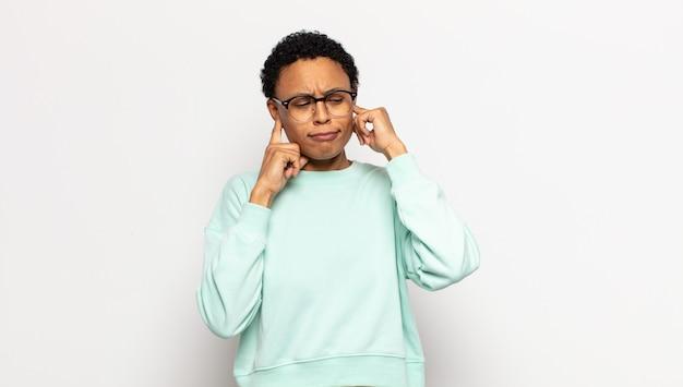 Junge afro-frau, die wütend, gestresst und genervt aussieht und beide ohren zu einem ohrenbetäubenden geräusch, ton oder laute musik bedeckt