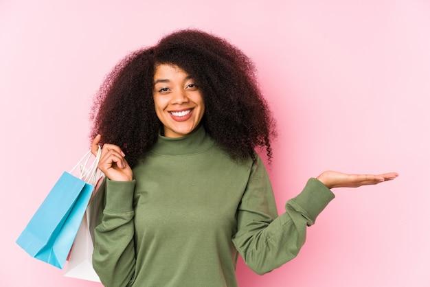 Junge afro frau einkaufen isoliert junge afro frau kaufen isolayoung afro frau hält eine rosen isoliert zeigt eine kopie platz auf einer handfläche und hält eine andere hand auf der taille. <mixto>