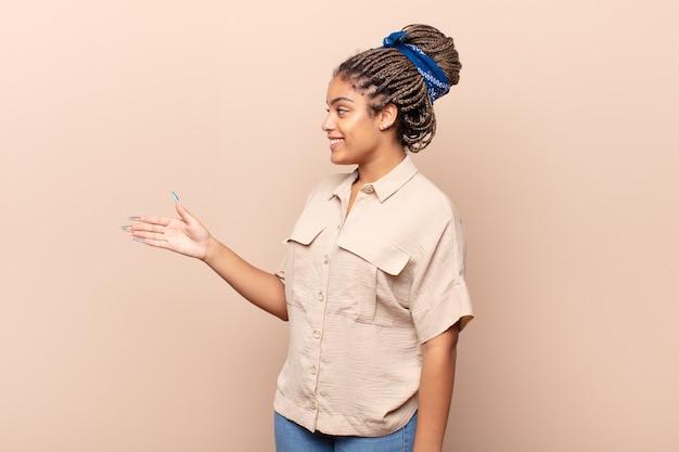 Junge afro-frau lächelt, begrüßt sie und bietet einen handschlag an, um einen erfolgreichen deal abzuschließen