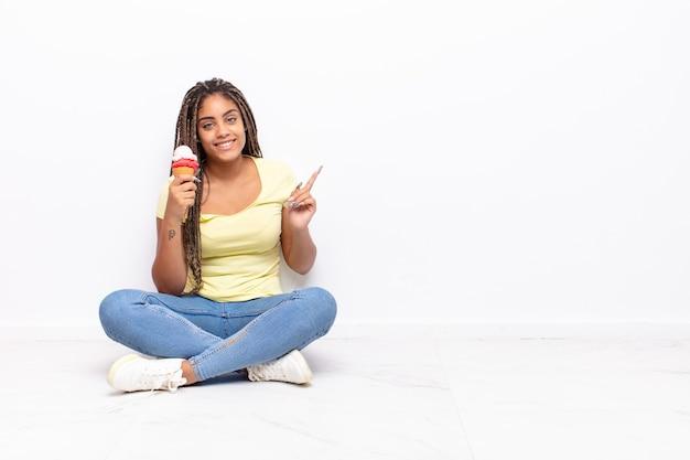 Junge afro-frau lächelt fröhlich, fühlt sich glücklich und zeigt zur seite und nach oben, zeigt objekt im kopierraum. eiscreme-konzept