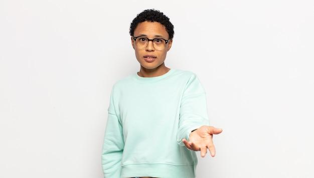 Junge afro-frau lächelt, sieht glücklich, selbstbewusst und freundlich aus und bietet einen handschlag an, um einen deal abzuschließen, kooperierend