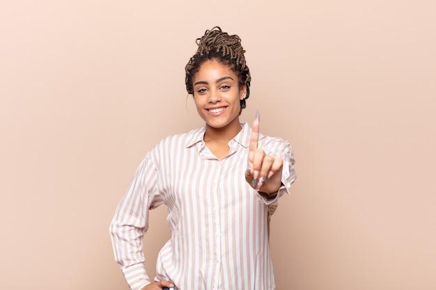 Junge afro-frau lächelt und sieht freundlich aus, zeigt nummer eins oder zuerst mit der hand nach vorne, zählt herunter