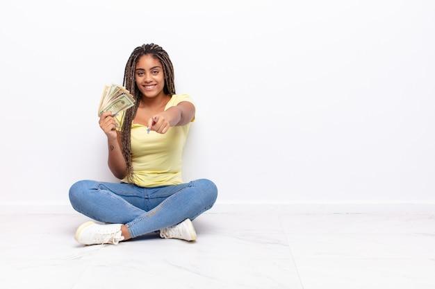 Junge afro-frau zeigt nach vorne mit einem zufriedenen, selbstbewussten, freundlichen lächeln und wählt sie. geldkonzept