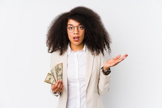 Junge afro-geschäftsfrau, die ein kreditauto hält, überrascht und schockiert.