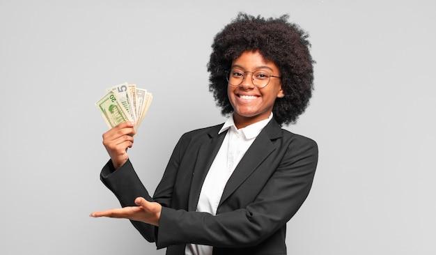 Junge afro-geschäftsfrau, die fröhlich lächelt, sich glücklich fühlt und ein konzept zeigt