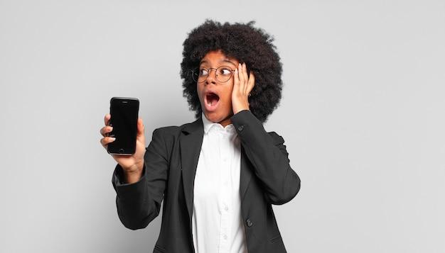 Junge afro-geschäftsfrau, die sich glücklich, aufgeregt und überrascht fühlt und mit beiden händen im gesicht zur seite schaut. unternehmenskonzept