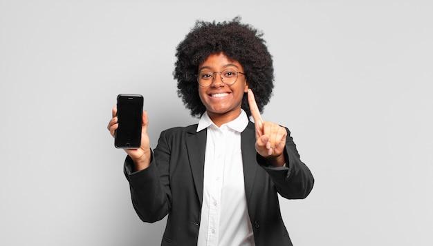 Junge afro-geschäftsfrau, die stolz und selbstbewusst lächelt und die nummer eins triumphierend posiert und sich wie ein anführer fühlt.
