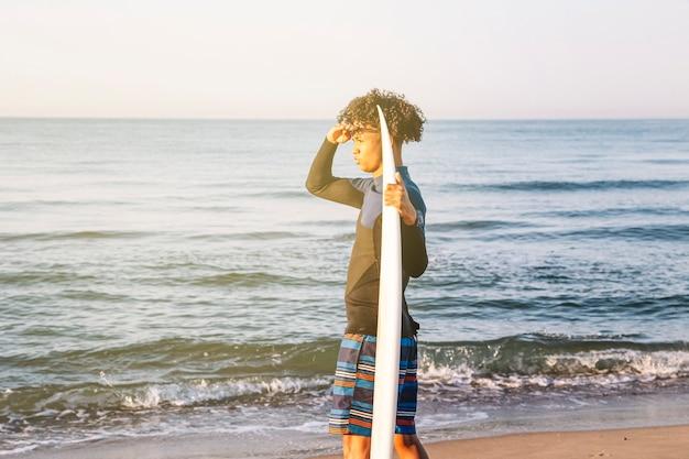 Junge afro-surfer mit surfbrettern mit blick auf den horizont am strand bei sonnenaufgang.