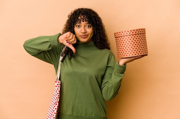 Junge afroamerikaner-afro-frau, die ein valentinstaggeschenk hält, das eine abneigungsgeste zeigt, daumen nach unten. uneinigkeit konzept.