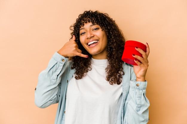 Junge afroamerikaner-afro-frau, die ein valentinstaggeschenk hält, das eine handy-anrufgeste mit den fingern zeigt.