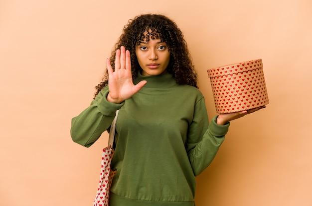 Junge afroamerikaner-afro-frau, die ein valentinstaggeschenk hält, das mit ausgestreckter hand steht, die stoppschild zeigt, das sie verhindert.