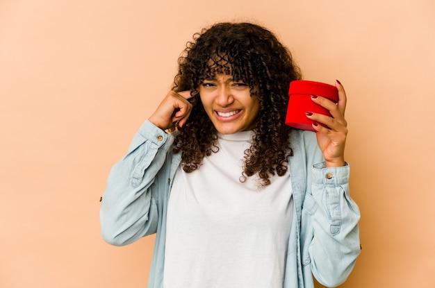 Junge afroamerikaner-afro-frau, die ein valentinstaggeschenk hält, das ohren mit händen bedeckt.