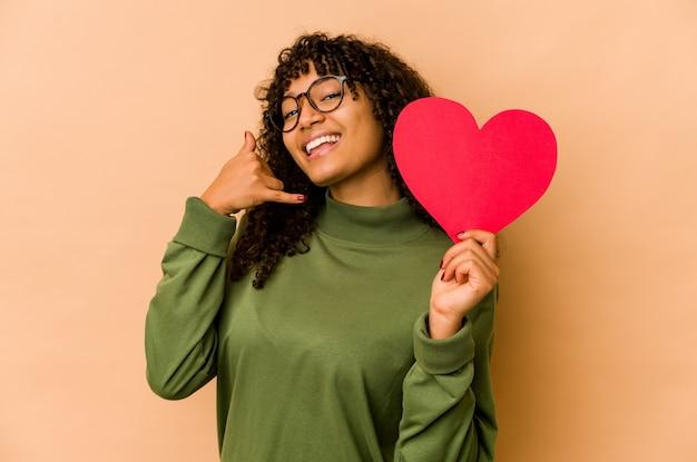 Junge afroamerikaner-afro-frau, die ein valentinstagherz hält, das eine handy-anrufgeste mit den fingern zeigt.