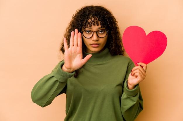 Junge afroamerikaner-afro-frau, die ein valentinstagherz hält, das mit ausgestreckter hand steht, die stoppschild zeigt, das sie verhindert.