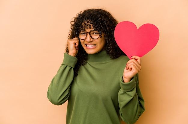 Junge afroamerikaner-afro-frau, die ein valentinstagherz hält, das ohren mit händen bedeckt.