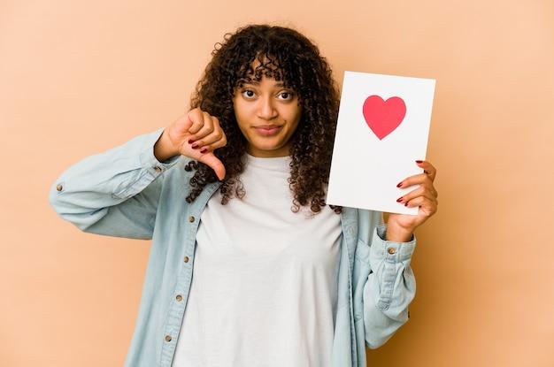 Junge afroamerikaner-afro-frau, die eine valentinstagskarte hält, die eine abneigungsgeste zeigt, daumen nach unten. uneinigkeit konzept.
