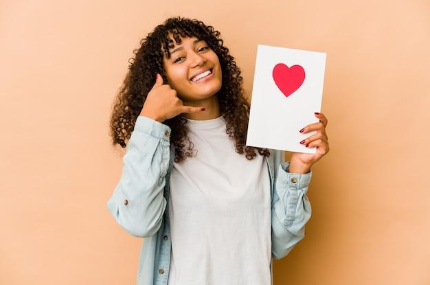 Junge afroamerikaner-afro-frau, die eine valentinstagskarte hält, die eine handy-anrufgeste mit den fingern zeigt.