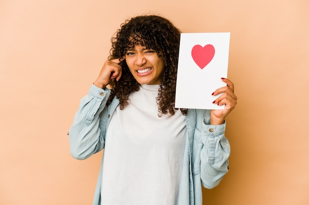 Junge afroamerikaner-afro-frau, die eine valentinstagskarte hält, die ohren mit händen bedeckt.